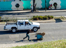 Street sweeper worker with his handcart. Santiago de Cuba, Cuba - January 11, 2016: Typical scene of one of streets in the center of Santiago de Cuba -people Royalty Free Stock Images