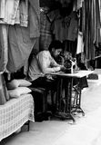 Street Taylor Working in India. A traditional street taylor works on clothing using a foot powered old style sewing machine stock photography