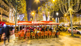 Street Terrace on Champs Elysees in a Winter Night. Paris,France - 27 November 2016: Unidentified people spending time on a street terrace on the famous Parisian Royalty Free Stock Photos