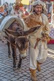 Street theater spectacle show, with actors walking the streets dressed in middle-aged costumes and holding donkeys also decorated stock photo