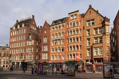 AMSTERDAM, NETHERLANDS - JUNE 25, 2017: View to the old historical buildings on the Damrak street in Amsterdam. On the street there are cultural centers, many Stock Image
