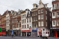 AMSTERDAM, NETHERLANDS - JUNE 25, 2017: View to the old historical buildings on the Damrak street in Amsterdam. On the street there are cultural centers, many Royalty Free Stock Image
