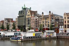 AMSTERDAM, NETHERLANDS - JUNE 25, 2017: View to the old historical buildings on the Damrak street in Amsterdam. On the street there are cultural centers, many Stock Photo