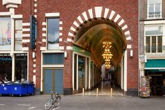 AMSTERDAM, NETHERLANDS - JUNE 25, 2017: View to the old arch in historical building on the Damrak street in center of Amsterdam. On the street there are museums Royalty Free Stock Photo