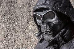 Street thug in a skull mask and hood royalty free stock photo