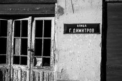 Street sign on abandoned ruined house. Street tinplate sign in Cyrillic G.Dimitrov on abandoned ruined house in small Bulgarian village, black and white image Royalty Free Stock Image