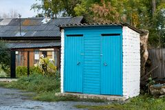 Street toilet. Overcast weather. Country buildings. Blue paint. Green trees Royalty Free Stock Photo