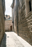 Street of  Toledo. Paved street of old houses and lamps in the Spanish city of Toledo, in the background you can see arabic gate Royalty Free Stock Images