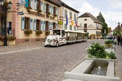 A street with a tourist train in Eguisheim village in France stock photography