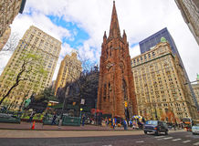 Street with tourists and traffic and Trinity Church in Manhattan Royalty Free Stock Photo