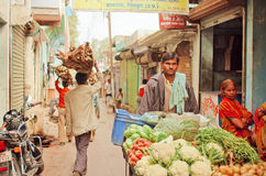 Street trader bringing carrots, zucchini, cauliflower to village vegetable market of indian city Royalty Free Stock Image