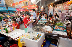 Street trader of seafood market with shrimps, brines, fish and meat Stock Photos