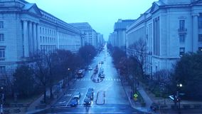 Rainy Washington DC in blue. Street traffic and pedestrians move along 10th Street NW in the nations capitol capital past the Internal Revenue Service IRS