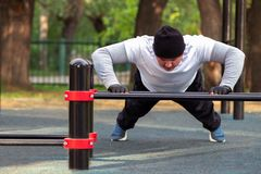 Street workout of a young man in the early sunny morning. A man performs an active power load on the simulator royalty free stock image