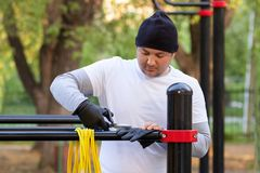 Street workout of a young man in the early sunny morning. The man is preparing to perform a power load on the simulator and cuts royalty free stock photography