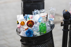 Street trash cans are filled with garbage cans with plastic bottles of scans up to the top. Stock Image
