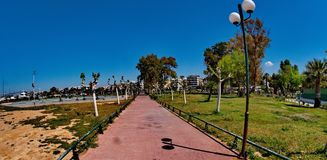 Street of trees and a lamp post. A picture of a lamp post and trees,in a pathway in a summer beach resort in Athens,Greece.in a summer day of april Royalty Free Stock Photo