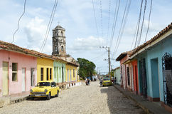 Street in Trinidad with Saint Anne church (Cuba). Typical street in Trinidad, with coloured houses, a yellow vintage taxi, unidentified people and Saint Anne Royalty Free Stock Image