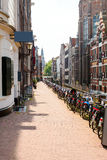 Street with typical Dutch houses and bicycles in Amsterdam. Stock Images