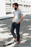Street urban old school sport at summer. Hipster skateboarder and skate at the street. Journey for adult beard man Royalty Free Stock Photos