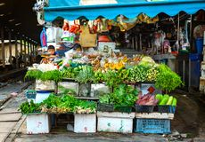 Street vegetable vendor next to railway station. Samutsakorn Province, Thailand - March 14, 2019: Daily life of street vendor selling variety of vegetables royalty free stock image