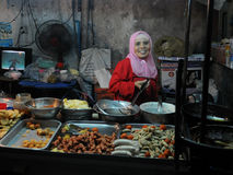Street Vendor. A street vendor cooks at a roadside restaurant at a night market on June 19, 2011 in Bangkok, Thailand. According to government figures there are Stock Photo