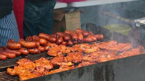 Street vendor cooking grilled food outdoors, unhealthy nutrition, fatty snacks. Stock footage stock video footage