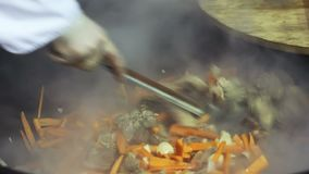 Street vendor cooking meat and vegetable mix at food festival, charity shelter. Stock footage stock video