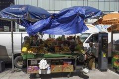 Street Vendor with Fruit Cart. New York, NY USA -- Aug 3, 2016   A street vendor sits by his fruit cart in Midtown amid heavy traffic. Editorial Use Only Stock Photo
