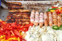 Street vendor grill with hot dogs and veggies. Bacon wrapped hot dogs, onions, jalapenos, and several varieties of bell peppers grilling on an outdoor vendors Royalty Free Stock Photos