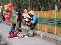 Street vendor in India. Poor family comprising of husband, wife and small kids selling balloons and other toys on the street in India Stock Photo