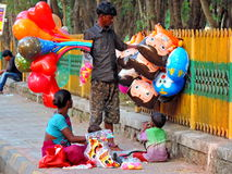 Street vendor in India. Poor family comprising of husband, wife and small kids selling balloons and other toys on the street in India Stock Image