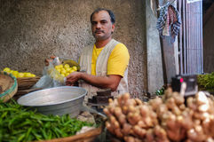 Street vendor. MUMBAI, INDIA - 11 JANUARY 2015: Vendor in Andheri fruit market putting lemons in bag Stock Photos