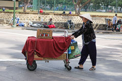 Street Vendor pushing cart across street. Female Chinese street vendor pushing cart covered with red cloth across street with homeless people in background Stock Photos