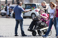 Street vendor of roses tries to sell a disabled lady. A Street vendor tries to sell you a pink rose to a disabled lady in a wheelchair / In the distance some Stock Photo