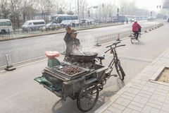 Street vendor selling chestnuts. BEIJING, CHINA-MARCH 2014:-The street vendor selling hot roast chestnuts China, March 2014 in Beijing. The street vendors do not Royalty Free Stock Images