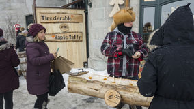 Street vendor selling maple toffee made of hot maple syrup in Quebec, Canada. Maple taffy sugar candy with a wooden popsicle stick on snow Stock Photos