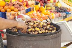 Street vendor selling roasted  chestnuts, Castanea, in autumn or Stock Images