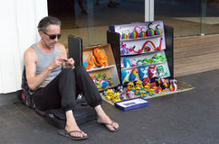 Street Vendor selling toys. Auckland - February 17, 2017: Street vendor sitting on the Queen Street selling puppets and toys Stock Photography