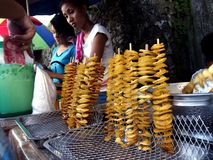 Street vendor sells fried potatoes on a stick Royalty Free Stock Image