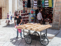 Street vendor sells sweets near the entrance to the Suq Aftimos market in Muristan Street in the old city of Jerusalem, Israel. Jerusalem, Israel, July 14, 2017 Stock Image