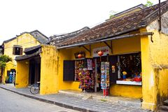 Street vendor with shoulder pole and conical hat in Hoi An Ancient Town, Quang Nam, Vietnam Stock Image