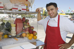 Street Vendor Standing By Stall stock photography