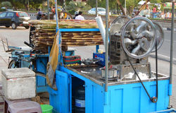 street vendor use machine to crush sugar cane to make juice on a cart Stock Photo