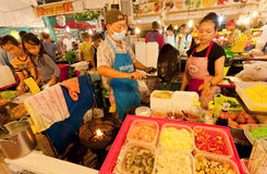 Street vendors and fast-food cookers sell exotic dishes with seafood and noodles on market Royalty Free Stock Images
