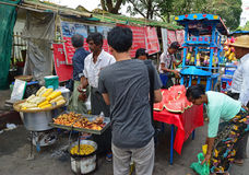 Street vendors selling sweet corn, cut red watermelon and vegetarian fritter to customers Stock Images