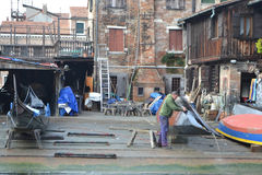 Street in Venice. Master repairing gondola. Stock Image