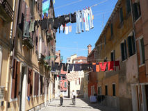 THE STREET IN VENICE. SMALL STREET IN VENICE, ITALY. CLOTHESLINES BETWEEN OLD HOUSES, WASHED CLOTHES HANGING ON CLOTHESLINES Royalty Free Stock Images
