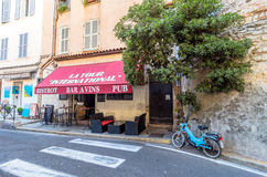 Street view in Antibes old town, France. Antibes, France - June 29, 2016: day view of typical street with bistrot in Antibes, France. Antibes is a popular Royalty Free Stock Photo
