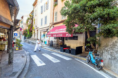 Street view in Antibes old town, France. Antibes, France - June 29, 2016: day view of typical street with bistrot in Antibes, France. Antibes is a popular Royalty Free Stock Photos